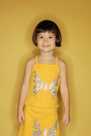 3 4 years: Young girl standing in front of yellow wall
