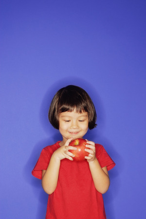 3 4 years: Young girl standing against blue background, holding an apple