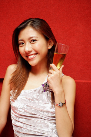 southeast asian ethnicity: Young woman holding champagne glass, smiling at camera