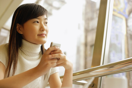 look pleased: Young woman holding mobile phone, looking away LANG_EVOIMAGES