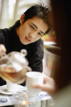 Young man pouring tea for young woman in front of him. LANG_EVOIMAGES