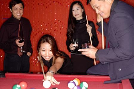 Men and women playing pool Stock Photo