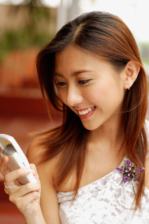 southeast asian ethnicity: Young woman holding mobile phone, smiling LANG_EVOIMAGES