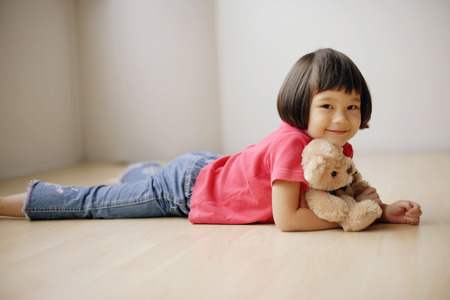 3 4 years: Young girl lying on front, hugging teddy bear. LANG_EVOIMAGES