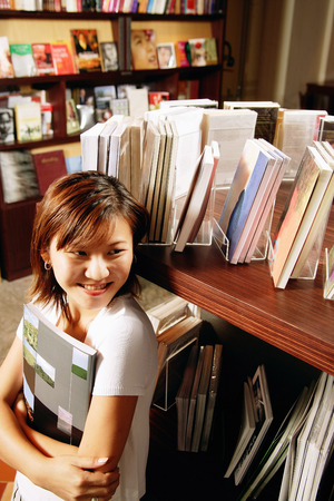 Young woman in bookstore, holding book, looking away