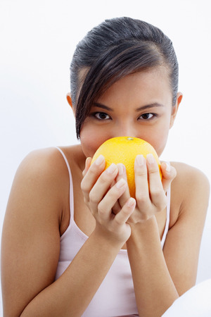 Woman holding orange to face