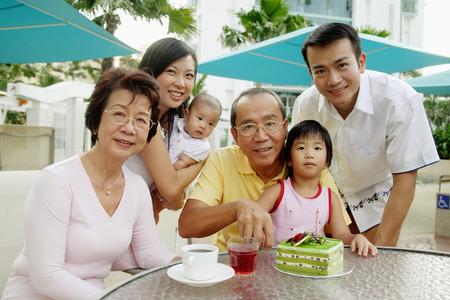 Famille de trois générations, grand-père coupe gâteau, regardant la caméra