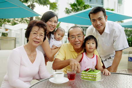 three generation: Three generation family, grandfather cutting cake, looking at camera