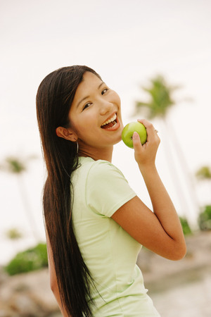 Woman with apple, looking at camera