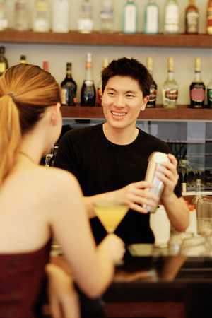 t bar: Man holding cocktail mixer, woman in front of him