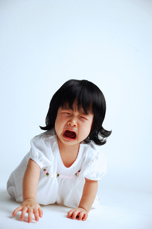 Bambina che striscia sul pavimento, piangendo, bocca aperta Archivio Fotografico - 67726346