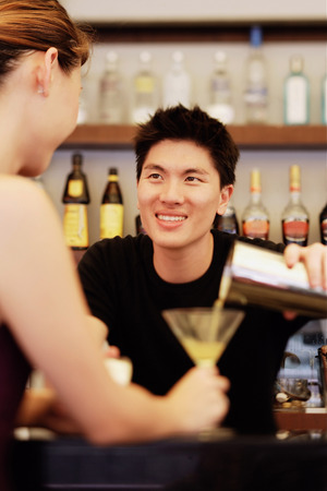 cocktail mixer: Man holding cocktail mixer, pouring drink for woman in front of him