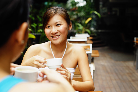 Young women having coffee, over the shoulder view Stock Photo