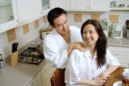 Couple in kitchen, man massaging womans shoulder