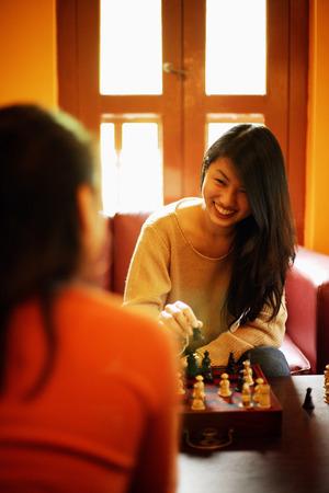 jugando ajedrez: Dos mujeres jóvenes jugando al ajedrez LANG_EVOIMAGES