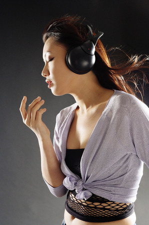 Young woman with headphones on, sideview