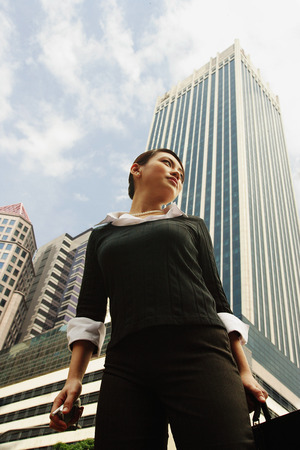 Business woman standing, looking away, buildings in the background