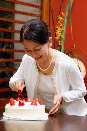Mature woman cutting birthday cake, smiling