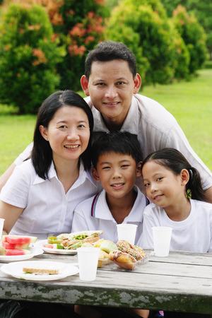 Family seated at picnic table, looking at camera
