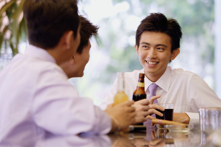 Young men at bar counter with drinks Imagens