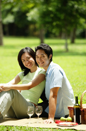Couple having picnic in park, looking at camera