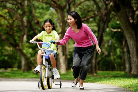 Girl on training bicycle, mother guiding her