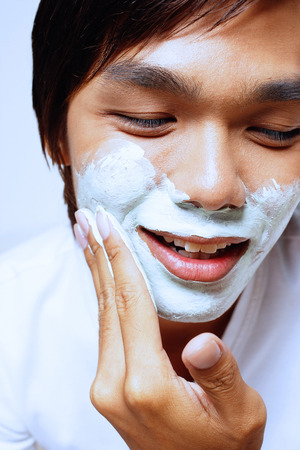 metrosexual: Young man applying shaving foam on face, looking down LANG_EVOIMAGES