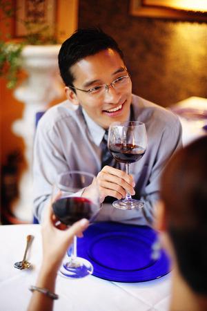 Couple in restaurant, holding wine glasses