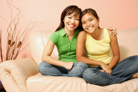 Mother and daughter, sitting on sofa, smiling