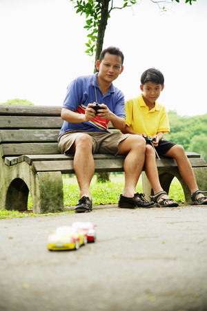 Father and son playing with remote control cars in the park