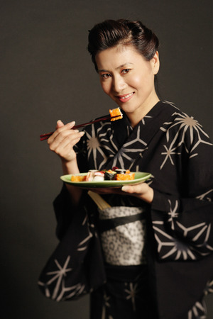 look pleased: Woman in Japanese costume, holding chopsticks and eating sushi LANG_EVOIMAGES