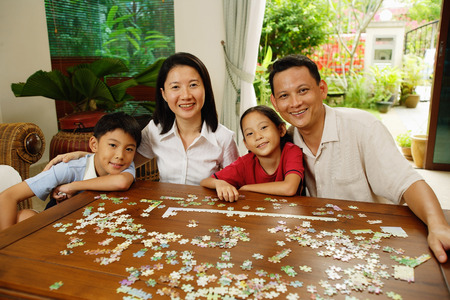 family  room: Family in living room, jigsaw puzzle on table, portrait
