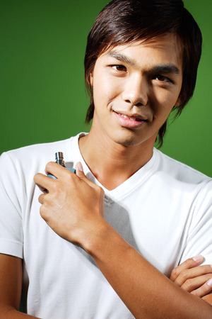 metrosexual: Young man looking at camera, holding bottle of perfume