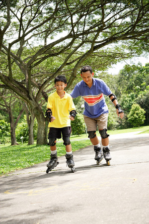 blading: Father and son roller blading in park