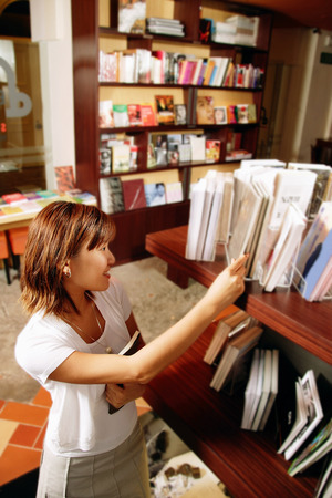 Young woman looking at books on bookshelf, high angle view
