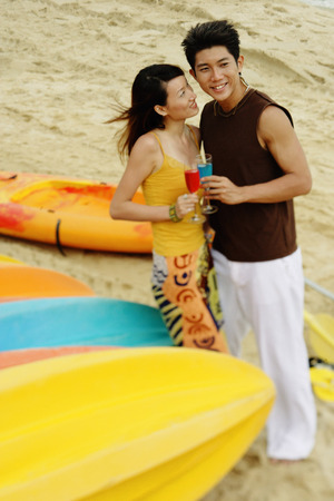 Couple on beach, holding drinks, looking away