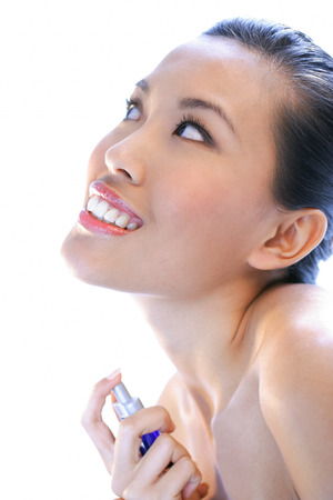 Woman applying perfume, looking up, smiling Stock Photo
