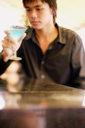Young man at bar counter holding and looking at cocktail glass