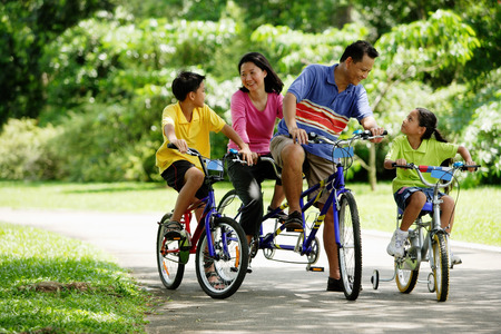 Family in park, riding bicycles Stock Photo