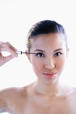 look pleased: Woman holding mascara wand, looking at camera LANG_EVOIMAGES