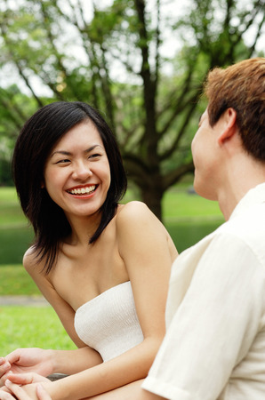Woman smiling at man sitting next to her Stock Photo