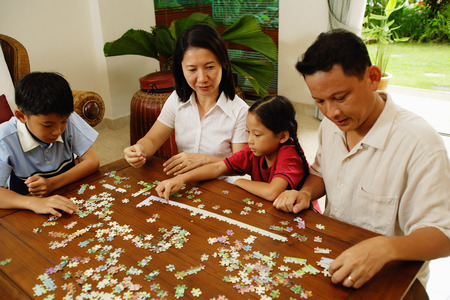 family  room: Family in living room working on jigsaw puzzle together LANG_EVOIMAGES
