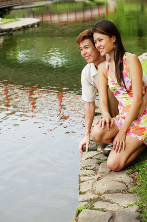 crouching: Couple crouching next to pond edge LANG_EVOIMAGES