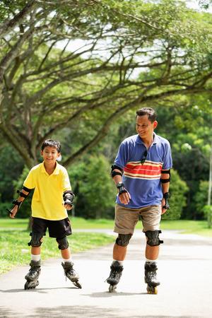 ローラーブレードの公園で父と子 写真素材