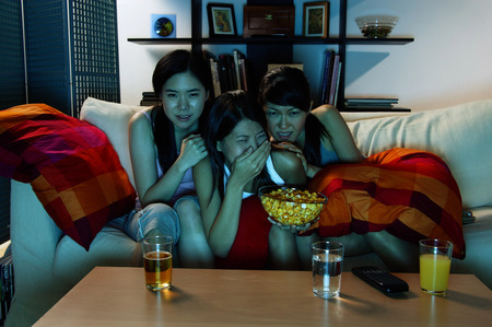 Three young women sitting on sofa in living room, watching TV