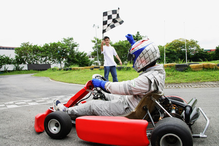 Young woman in go-cart, young man waving flag LANG_EVOIMAGES