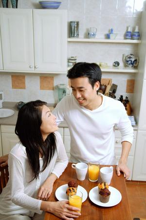 お互いに笑みを浮かべて、キッチンで朝食を持っているカップル