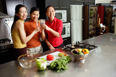 Women in kitchen, toasting, smiling at camera Imagens