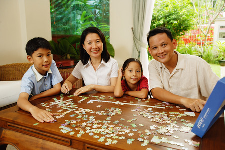 family  room: Family in living room, jigsaw puzzle on table LANG_EVOIMAGES