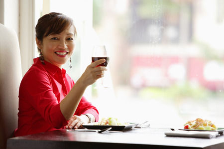 Woman sitting at table, raising drink towards camera, smiling Stock Photo